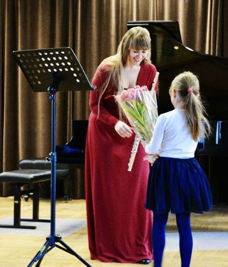 Warsaw flute lessons agnieszka rogowiecka, flute teacher holds the flowers from student